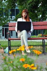 Girl on a bench with a laptop