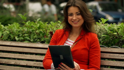 Joyful woman using tablet and smiling to the camera on bench