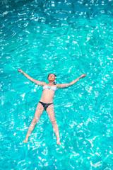 girl in bikini relaxing in the pool in the shape of a star