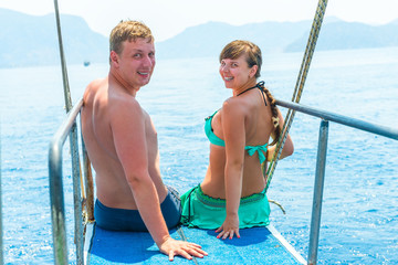 young couple in swimsuits on a yacht at sea