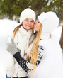 Young blond mother kissing her little daughter outdoors