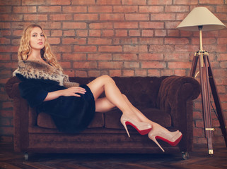 Beautiful woman in fur coat sitting on the sofa