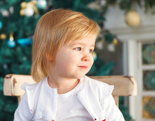 Cute Christmas baby by the Christmas tree