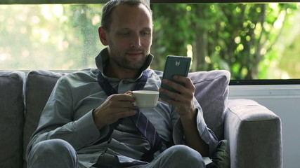 Happy businessman drinking coffee and texting, steadycam shot