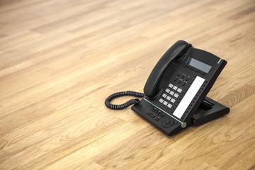 schwarzes Telefon auf Holzboden © Matthias Buehner