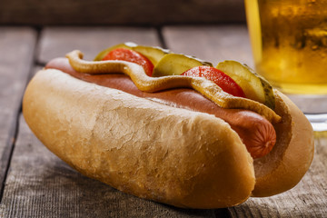 hot dog with mustard, pickles and tomatoes