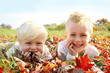 Two Happy Young Children Playing Outside in Fall Leaves - 72110738