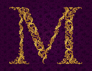 Gold font type letter M, uppercase.