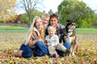 Leinwanddruck Bild - Happy Family and Pet Dog Autumn Portrait