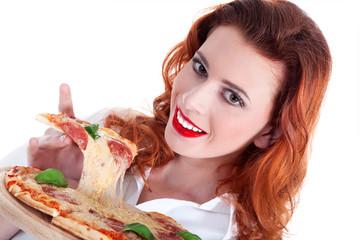 Rothaarige junge Frau isst ein Stück Salami Pizza