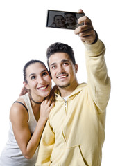 Young couple with smart phone taking selfie