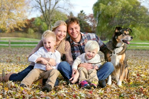 Leinwanddruck Bild Happy Family and Pet Dog Autumn Portrait