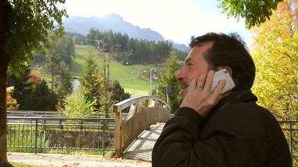 Happy man on the phone in front of amazing mountain