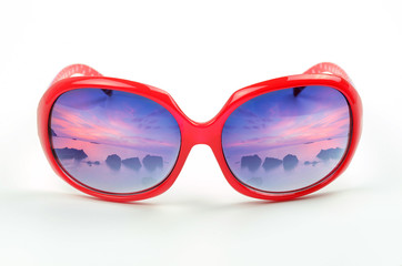 red sunglasses with a reflection of a beautiful  sea scape