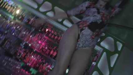 Go-go dancer with fit body dancing on club bar counter