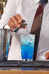 Barman preparando un coctel azul.