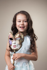 Cheerful little girl posing with carnival mask