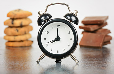 Black alarm clock with sweets