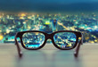 canvas print picture - Night cityscape focused in glasses lenses