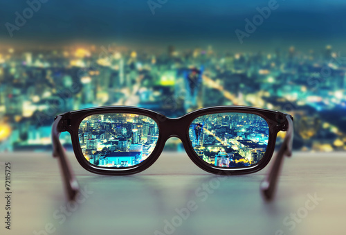 Fototapeta Night cityscape focused in glasses lenses