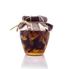 Honey jar with hazels, walnuts and raisins