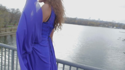 Young beautiful lady posing for camera on bridge, sweet sadness