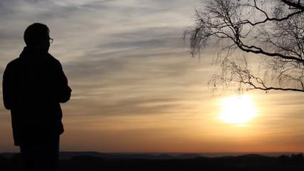 Mann mit Fernglas beim Sonnenuntergang