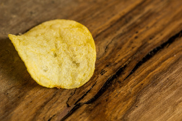 Potato chips on rustic background