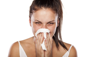 cold woman snorts in a napkin