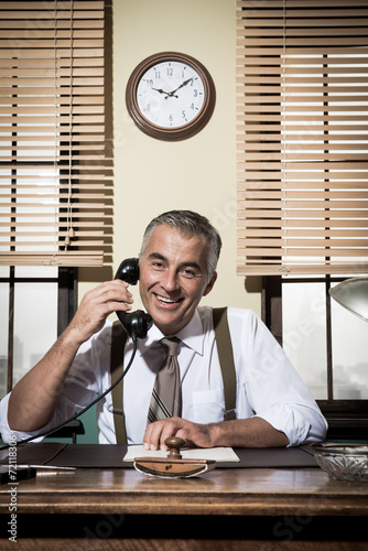 1950s smiling businessman on the phone - 72118306