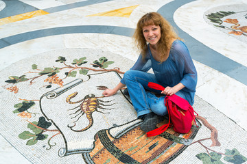 Female tourist on the Zodiac sign Scorpio in Galleria Umberto I