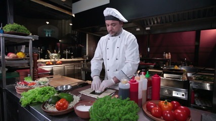 Smiling cook making sushi roll, fresh sushi ingredients on table