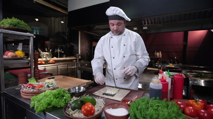 Sushi chef making sushi rolls with cucumber, restaurant kitchen