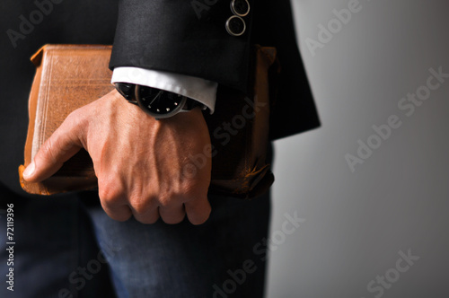 A businessman in a suit and jeans holding book - 72119396
