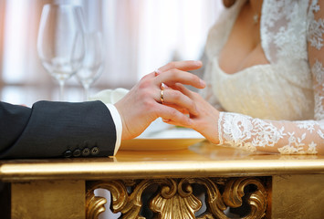 Hands of bride and groom at the wedding