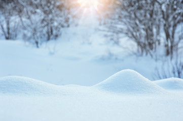 Winter background with a snowdrift and sun