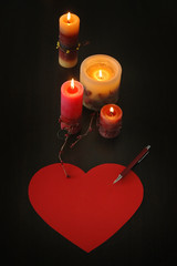 love letter in shape of heart with candles and pen