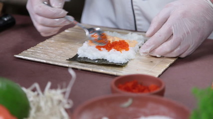 Cook making Japanese sushi rolls with caviar, cooking process