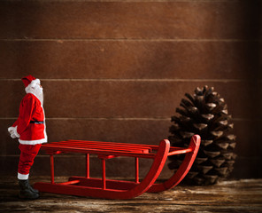 Red sled with pine cone and Santa Claus
