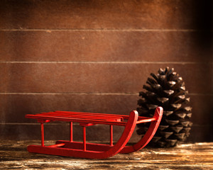 Wooden red sled with brown pine cone