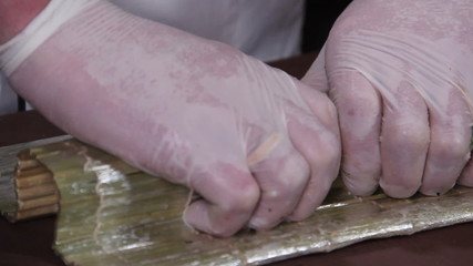 Close-up cook making Japanese sushi rolls on a bamboo mat