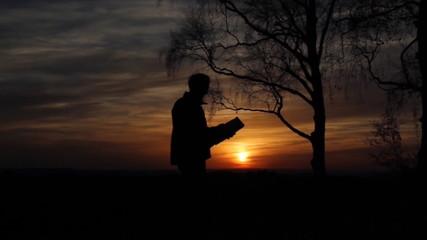 Mann orientiert sich mit einer Karte bei Sonnenuntergang