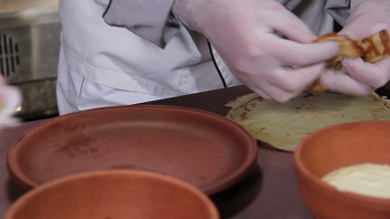 Close-up creative cook presenting dessert pancakes on a plate