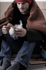 Cold and sad homeless man is eating a bread