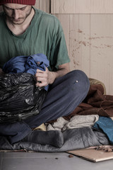 Homeless man looks a bag of clothes