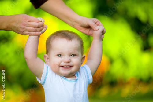 Leinwanddruck Bild Smiling happy baby learning to walk outdoors
