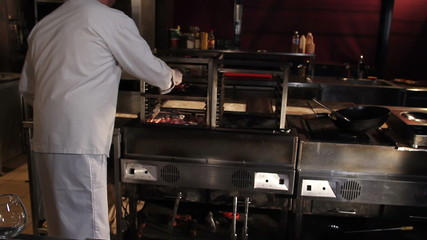 Chef putting spiced meat on the charcoal grill in restaurant