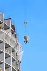 Crane lifting concrete mixer container against blue sky