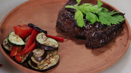 Cook serving sizzling hot steak on a plate with vegetables