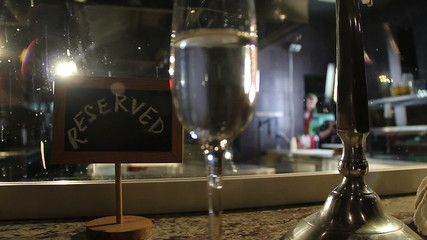 Champagne glass on reserved table, dim lights of restaurant